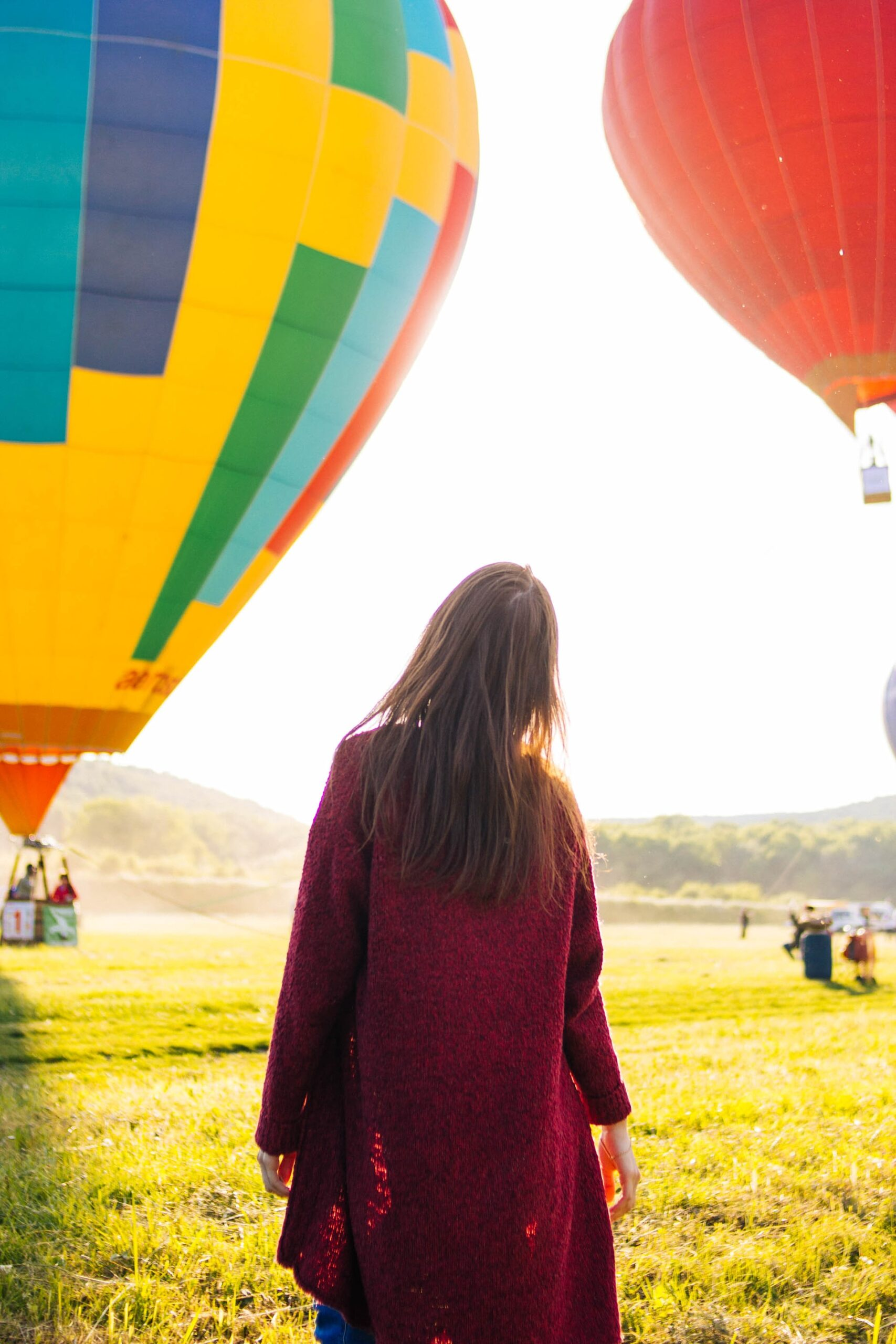 woman in a field with air balloons